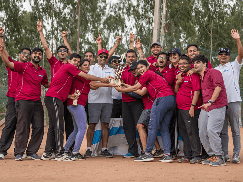 Zinnov Employees Celebrating Victory and Holding Prize at Big Bash Cricket Championship